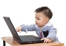 Menino que usa um computador portátil Fotografia de Stock Royalty Free