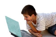 Menino que usa um portátil fotos de stock royalty free