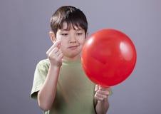 Menino que vai estalar o balão fotografia de stock royalty free