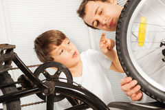 Menino que verifica as rodas da bicicleta com seu pai Fotos de Stock Royalty Free