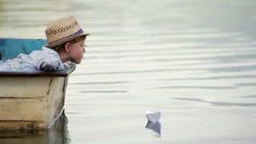 Menino que veste o chapéu de vime que senta-se no barco que ajusta seu barco de papel em uma viagem