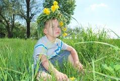Menino que veste uma coroa das flores Fotografia de Stock Royalty Free