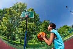 Menino árabe pronto para jogar a bola no objetivo do basquetebol Fotos de Stock Royalty Free