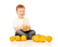Menino Red-haired com sumo de laranja e laranjas fotografia de stock royalty free