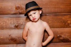 Menino ressentido no chapéu no fundo da parede de madeira imagens de stock