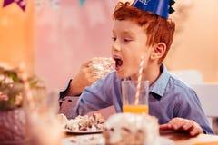 Menino ruivo com fome que come o bolo de aniversário saboroso imagens de stock royalty free