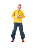 Menino ruivo novo em um menino de salto do revestimento amarelo com as mãos apertadas em um punho e levantadas seu polegar acima Foto de Stock Royalty Free