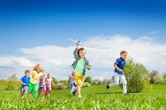 Menino running com brinquedo do avião e outras crianças imagens de stock royalty free