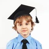 Menino sério pequeno no chapéu acadêmico no fundo branco imagem de stock royalty free
