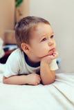 Menino sério pequeno que mantem suas mãos no queixo Imagens de Stock