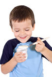 Menino saudável feliz que come o yogurt Imagens de Stock