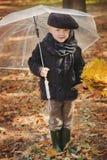 Menino sob o guarda-chuva no outono com folha amarela Imagem de Stock Royalty Free