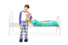 Menino sonolento que está na frente de uma cama Fotos de Stock Royalty Free