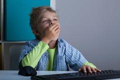 Menino sonolento que joga no computador Fotografia de Stock