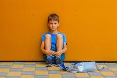 Menino sozinho triste que senta-se perto da parede colorida fora foto de stock royalty free