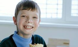 Menino sujo da criança de sete anos que come um gelado que está na janela Foto de Stock