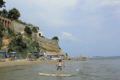 Menino surfando no mar de Nettuno Costa e praia italianas Destino do turista fotos de stock royalty free
