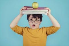 Menino surpreendido com livros e maçã imagem de stock royalty free