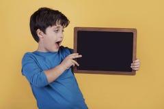 Menino surpreendido com um quadro-negro Imagem de Stock