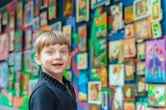 Menino surpreendido e alegre em uma exposição das pinturas na galeria de arte imagem de stock royalty free