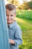 Menino tímido atrás do celeiro fotografia de stock