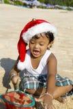 Menino tailandês com o chapéu do Natal na praia Fotos de Stock Royalty Free