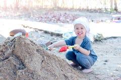 Menino tailandês que palying na pilha da areia com a forquilha do brinquedo e do plástico, sp Fotos de Stock Royalty Free