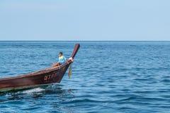 Menino tailandês que senta-se na cabeça do barco da cauda longa foto de stock