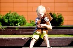 Menino triste adorável com o urso de peluche no parque fotos de stock royalty free