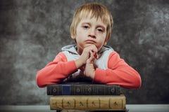 Menino triste 5 anos de assento velho com os livros, aprendendo o conceito Fotos de Stock Royalty Free