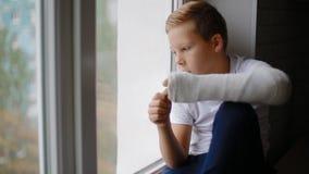 Menino triste com a mão quebrada que olha a janela video estoque