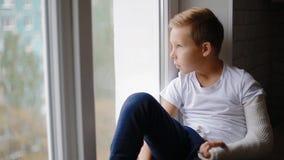 Menino triste com a mão quebrada que olha a janela vídeos de arquivo