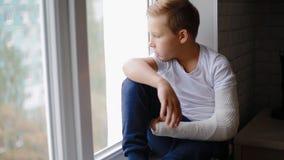 Menino triste com a mão quebrada que olha a janela filme