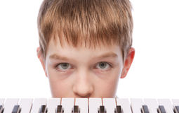 Menino triste perto do teclado de piano Imagem de Stock