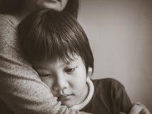 Menino triste preto e branco que está sendo abraçado por sua mãe em casa fotos de stock royalty free