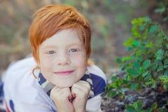 Menino vermelho bonito do cabelo que sorri à câmera e à posição na floresta com cavalo fotografia de stock
