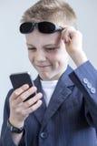 Menino vestido como o espião que usa um smartphone Fotografia de Stock Royalty Free