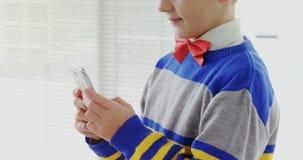 Menino vestido como o executivo que usa seu telefone celular 4K 4k vídeos de arquivo