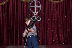 Menino vestido como o palhaço Holding Large Gun na fase Fotografia de Stock
