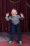 Menino vestido como o palhaço Acting Silly na fase Foto de Stock Royalty Free