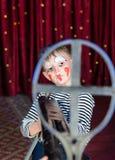 Menino vestido como o rifle de Aiming Over Sized do palhaço Fotografia de Stock