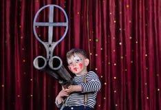 Menino vestido como o rifle de Aiming Over Sized do palhaço Imagem de Stock Royalty Free