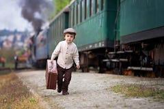 Menino, vestido na camisa do vintage e no chapéu, com mala de viagem Fotos de Stock