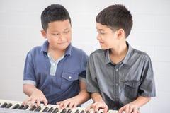 Meninos asiáticos do estudante que jogam o piano junto na classe foto de stock