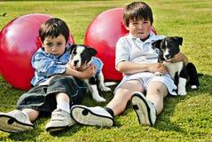 Meninos com animais de estimação do filhote de cachorro Fotos de Stock