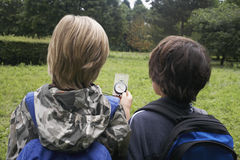 Meninos com trouxas usando o compasso Imagens de Stock Royalty Free