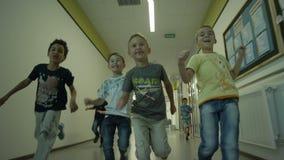 Meninos corridos ao longo brilhantemente do corredor largo do Lit no jardim de infância video estoque