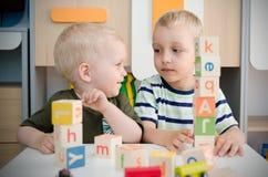 Meninos das crianças que jogam com blocos do brinquedo em casa ou jardim de infância Imagens de Stock Royalty Free