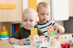 Meninos das crianças que jogam com blocos do brinquedo em casa ou jardim de infância Foto de Stock Royalty Free