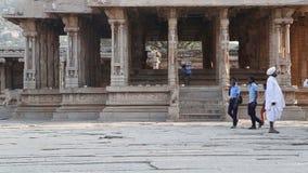 Meninos de escola indianos em camisas azuis que andam na frente da construção em Hampi video estoque